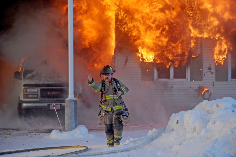 Staff photo by Michael G. Seamans CHRISTMAS FIRE: A Waterville firefighter gestures to other firefighters after arriving at an active fire at 160 Drummond Ave. in Waterville on Wednesday.