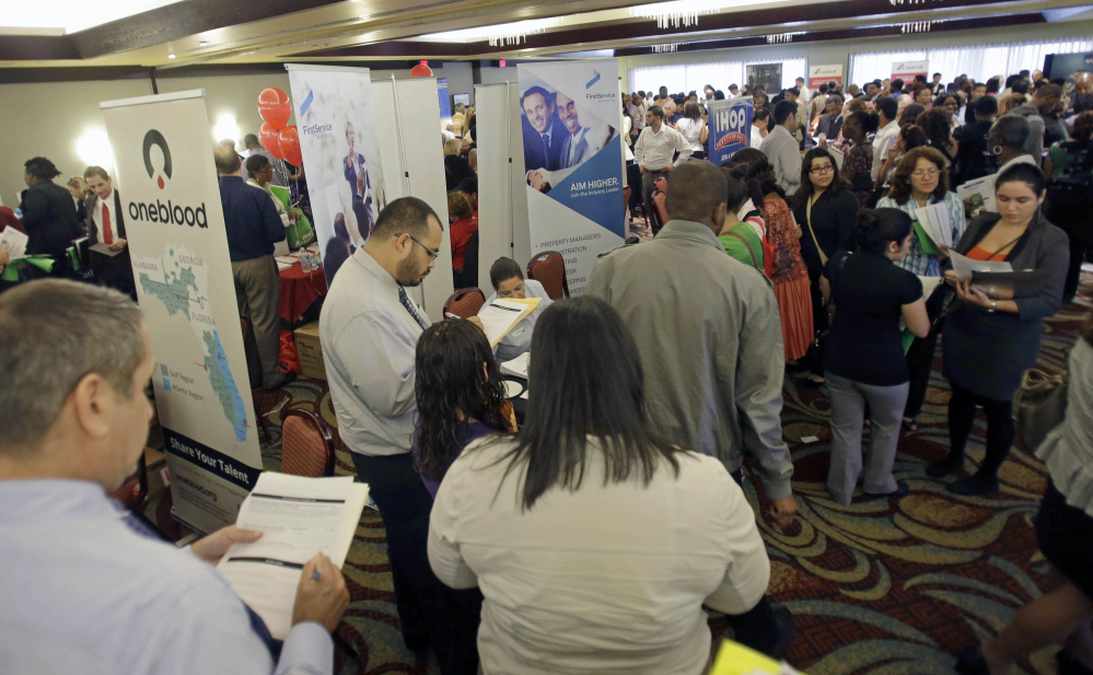 This Aug. 14, 2013 file photo shows job seekers checking out companies at a job fair in Miami Lakes, Fla. More than 1 million Americans are bracing for a harrowing, post-Christmas jolt as federal unemployment benefits come to a sudden halt this weekend. The development entails potentially significant implications for the recovering U.S. economy and sets up a tense battle when Congress reconvenes in the new year.