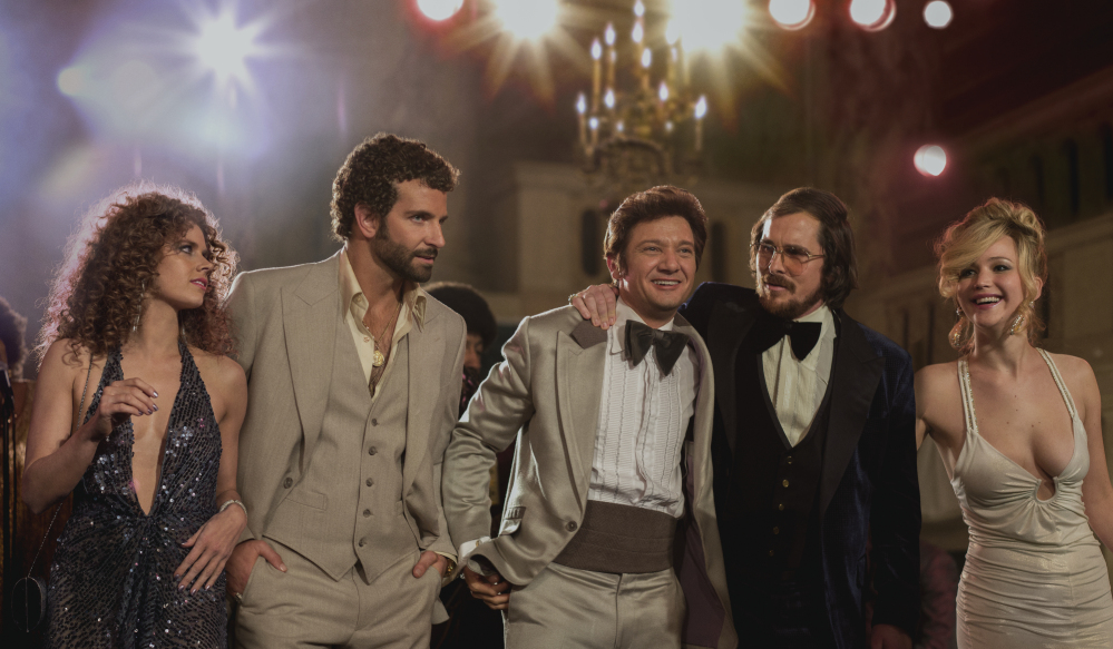 """This film image released by Sony Pictures shows, from left, Amy Adams, as Sydney Prosser, Bradley Cooper, as Richie Dimaso , Jeremy Renner, as Mayor Carmine Polito, Christian Bale as Irving Rosenfeld, and Jennifer Lawrence as Rosalyn Rosenfeld, in a scene from """"American Hustle."""" From Baleís burgundy velour blazer to Adamsí plunging sequin halter dress, the film is a cinematic romp through the over-the-top styles of the late 1970s. Hair is so prominent in the picture, itís practically another character."""