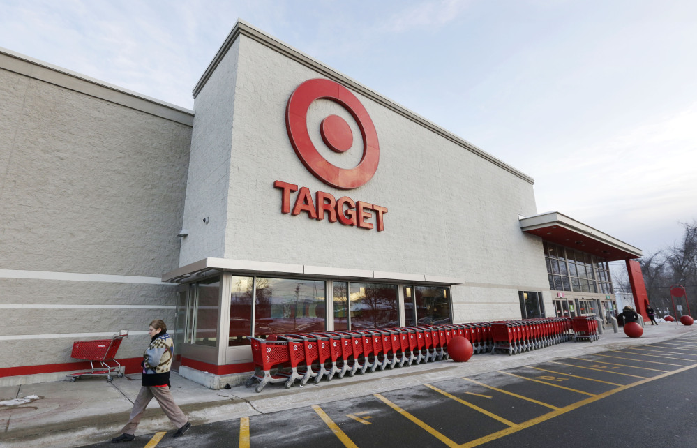 A passer-by walks near an entrance to a Target retail store in Watertown, Mass., this month. Target on Friday said customers' encrypted PIN data was removed during the data breach that occurred earlier this month. But the company says it believes the PIN numbers are still safe because the information was strongly encrypted.