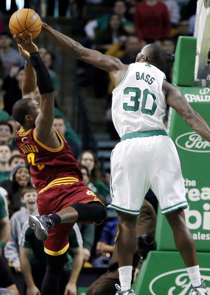 Boston Celtics' Brandon Bass (30) blocks a shot by Cleveland Cavaliers' Dion Waiters (3) with seconds left on the clock in the third quarter of an NBA basketball game in Boston, Saturday, Dec. 28, 2013. The Celtics won 103-100. (AP Photo/Michael Dwyer)
