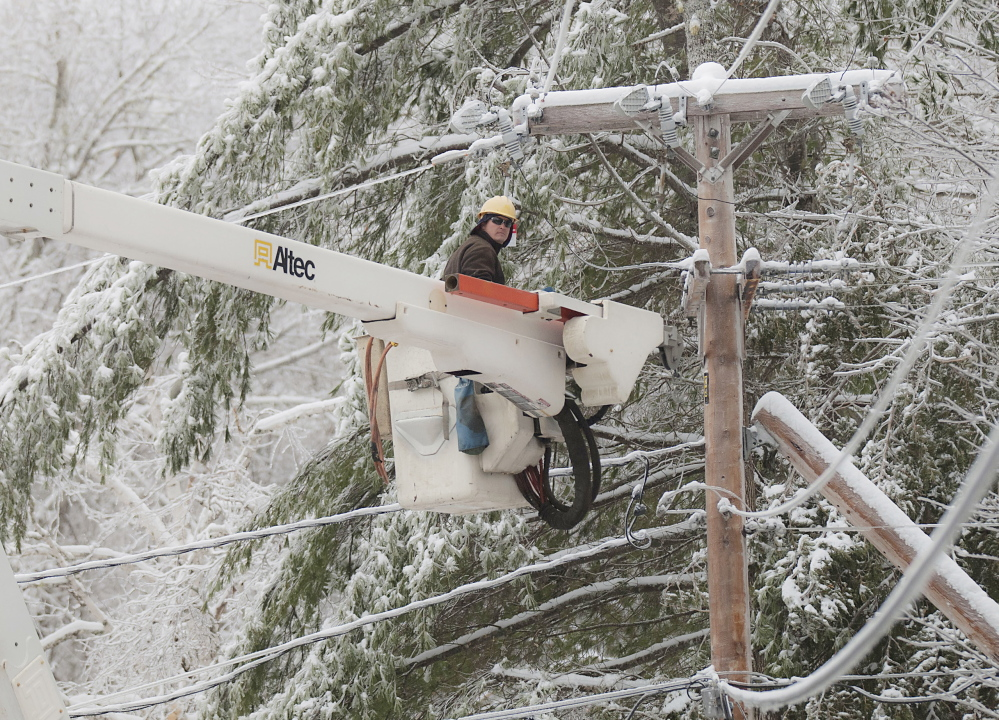 Maine Public Service lineman Craig Hobbs works to restore power on the Perkins Point Road off Brewer Lake in Orrington onSunday, Dec. 29. 2013.
