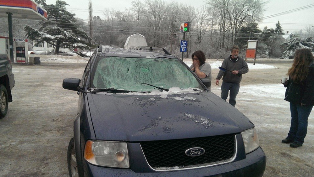 People check out a car hit by ice on the Penobscot Narrows Bridge on Sunday.