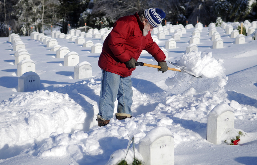 "TUNNEL OF LOVE: Paul Drouin shovels a path Monday to the grave of his wife, Patricia, at the Maine Veterans Memorial Cemetery in Augusta. ""She was more than my wife,"" the 74-year-old who visits twice a day said. ""She was my best friend."""