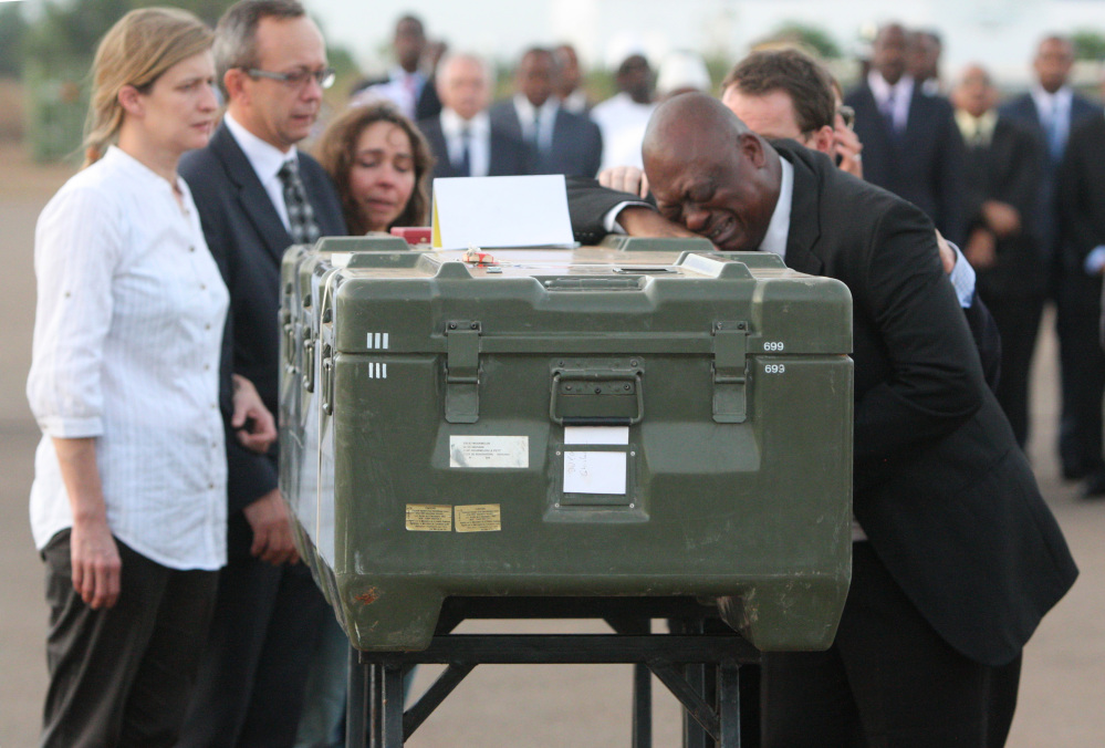 This Nov. 4, 2013 file photo shows Serge Daniel, right, Mali correspondent for Radio France Internationale weeping as he pays his last respects at the coffin of one of the two French journalists kidnapped and executed in northern Mali.