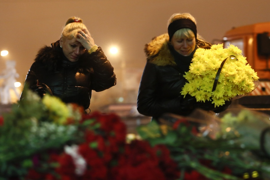Women cry as they lay flowers outside the Volgograd main railway station in Volgograd, Russia, early Monday. Russian authorities ordered police to beef up security at train stations and other facilities across the country after two bombing attacks in two days in the southern city of Volgograd.