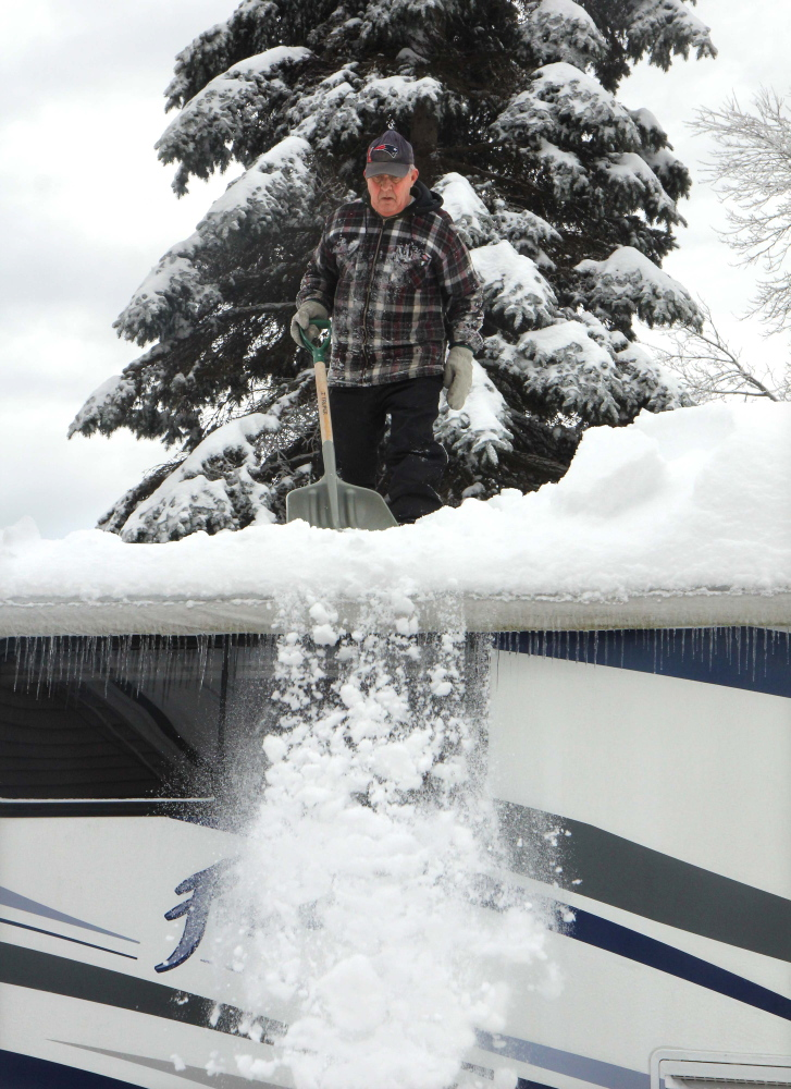"""CLEARING THE ROOF: Eric Blier of Waterville clears snow off the roof of his motor home that fell during Sunday night's storm next to his house on Cool Street in Waterville on Monday. Blier said he measured 14 inches of snow on top of his roof. Blier's wife, Carol, said the couple would normally be in Florida right now, but because she's battling cancer, they hope to get down there in the next month or so. """"I wanted to get up there and help, but he wouldn't let me,"""" said Carol."""