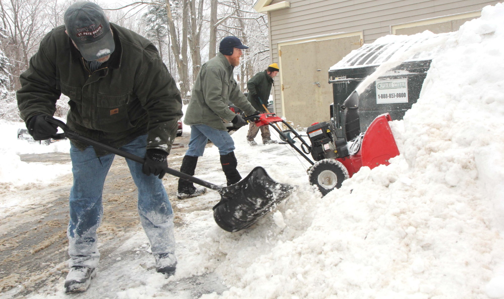 A TEAM EFFORT: Steve Schmidt, center, along with Scott Berry, left, and Ryan Doyon, far right, work to clear a parking lot behind an apartment building owned and operated by Kennebec Behavioral Health on Silver Street in Waterville on Monday. Sunday night's fast-moving storm dumped close to a foot of snow in many locales in central Maine.