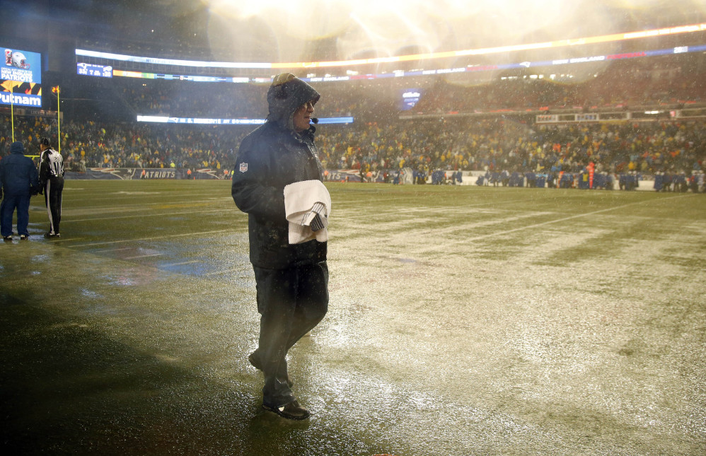 New England Patriots head coach Bill Belichick walks along the sideline of a rain-drenched field in the fourth quarter of an NFL football game against the Buffalo Bills, Sunday, Dec. 29, 2013, in Foxborough, Mass. The Patriots won 34-20, and will have a first-round bye in the AFC playoffs. (AP Photo/Elise Amendola)