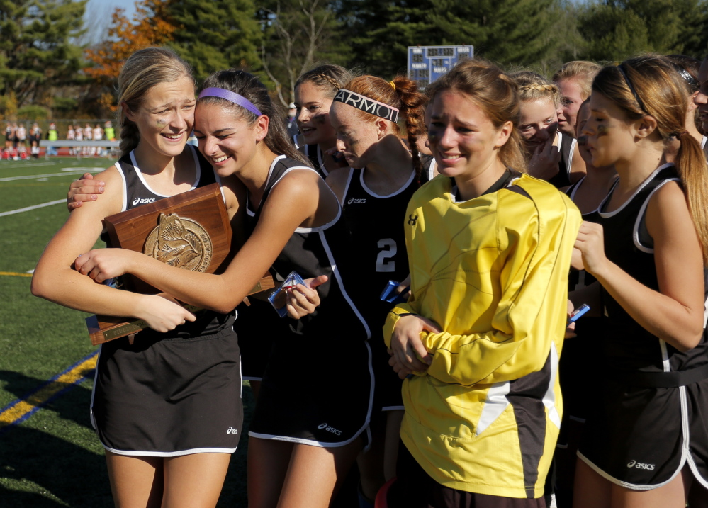 Gabe Souza/Staff Photographer Skowhegan's Mikayla Toh, left, receives a hug from Rylie Blanchet, as the Indians celebrate their win over Scarborough in the Class A field hockey championship at Yarmouth High School Saturday, November 2, 2013.