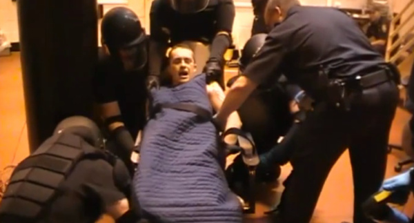 Paul Schlosser III is restrained after being removed from his cell.