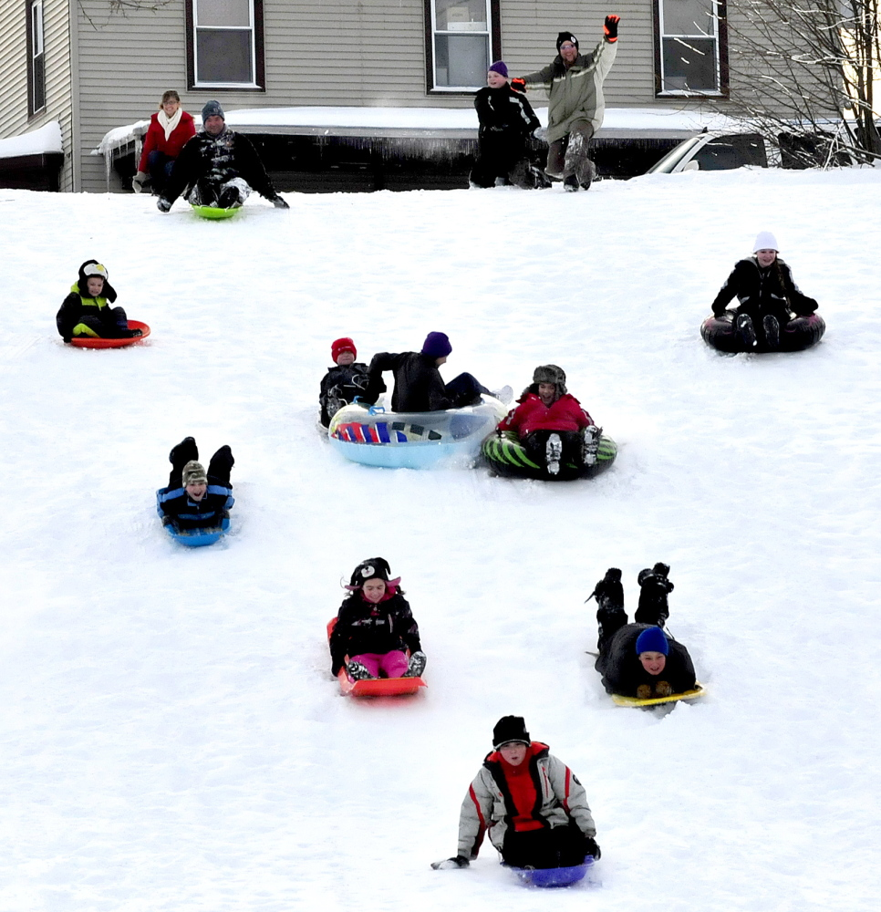 Staff photo by David Leaming WINTER FUN: Kids and adults race down the hill off Sherwin Street on sleds and tubes during the Inland Hospital sponsored Let's Go! Winter Fest in Waterville on Sunday, Jan. 5, 2014. People played outdoors sledding, snowshoeing and cross-country skiing.