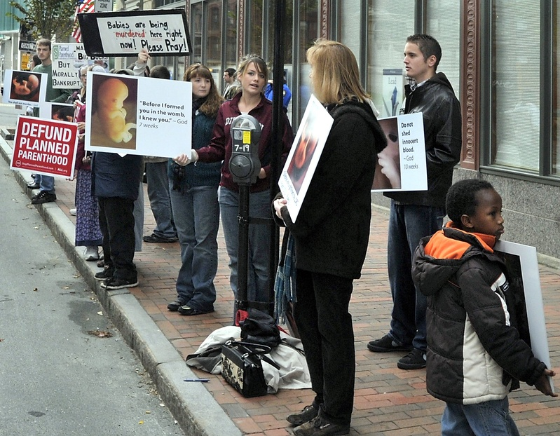 Anti-abortion demonstrators protest with graphic signs outside the Planned Parenthood of New England agency on Congress Street in Portland last year. The U.S. Supreme Court is hearing a challenge to a Massachusetts law similar to a Portland ordinance that restricts protests outside abortion clinics within a 39-foot buffer zone.