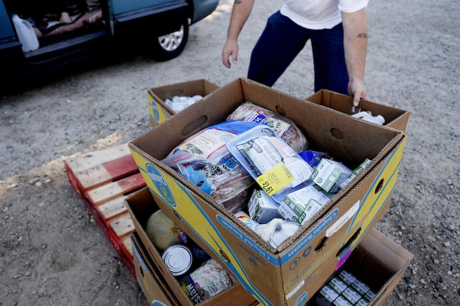 A volunteer grabs a box of food to give to seniors in need at the Good Shepherd Food-Bank Senior Food Mobile event. .