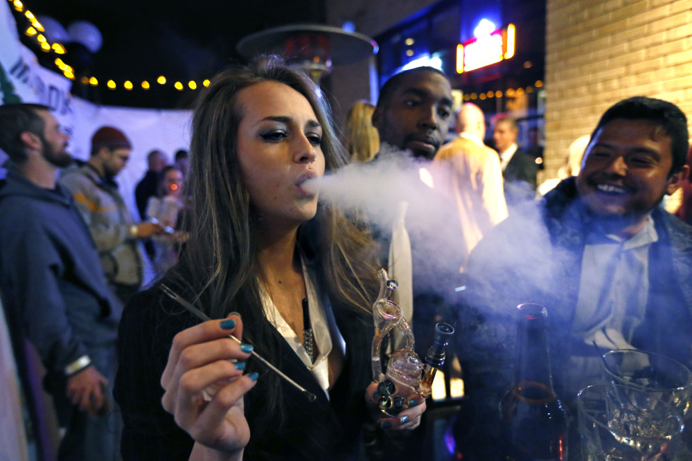 Partygoers smoke marijuana during a Prohibition-era themed New Year's Eve party celebrating the start of retail pot sales, at a bar in Denver, late Tuesday.