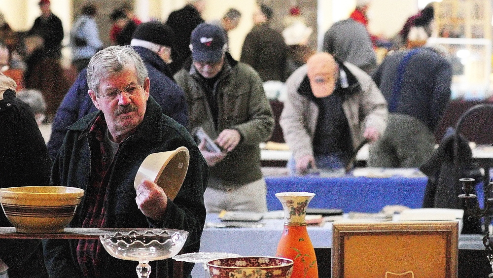 FORAGING: Dennis Ladd, of Farmingdale, looks at a bowl during the New Year's Antiques Show on Wednesday at the Augusta State Armory.