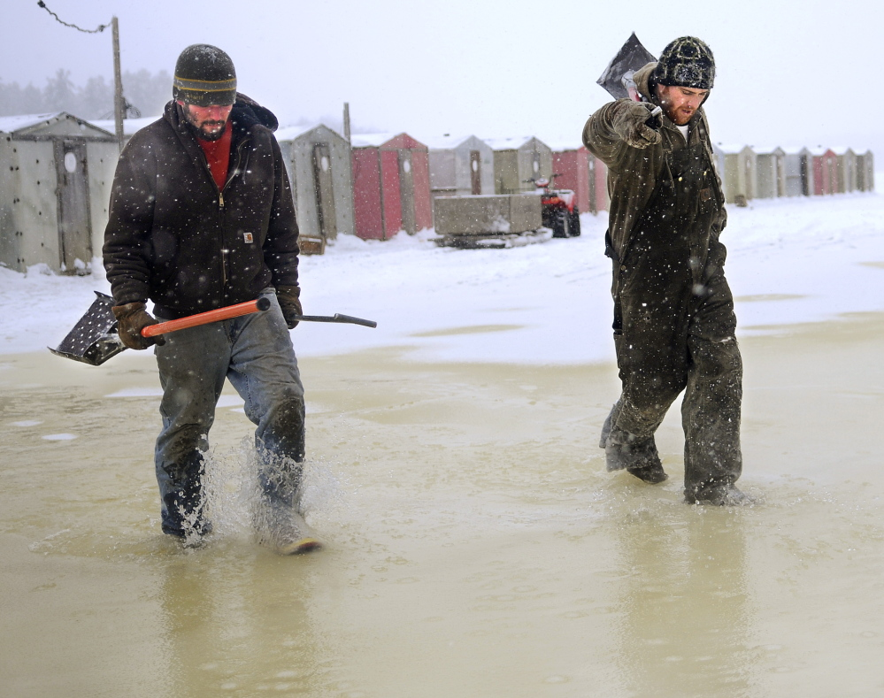 FISHING TIME: Mike Abbott, left, and Brandon Sutherburg walk through tidal slush to shore Thursday at Baker's Smelt Camps in Pittston. The men had broken open frozen race holes and cleaned the camps on the Kennebec River in sub-zero temperatures.
