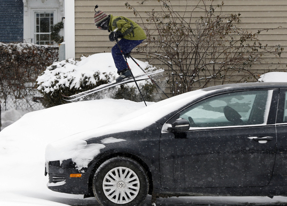 Milo Bloom, 10, skis over a snowbank next to a parked car during a snowstorm Thursday in Portland. Strong winds are creating blizzard-like conditions. A wind chill factor of 30 degrees below zero is expected Friday.