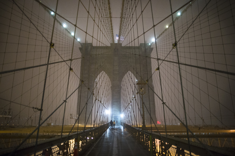 Pedestrians pass along a walkway under falling snow on the Brooklyn Bridge, Friday in New York.