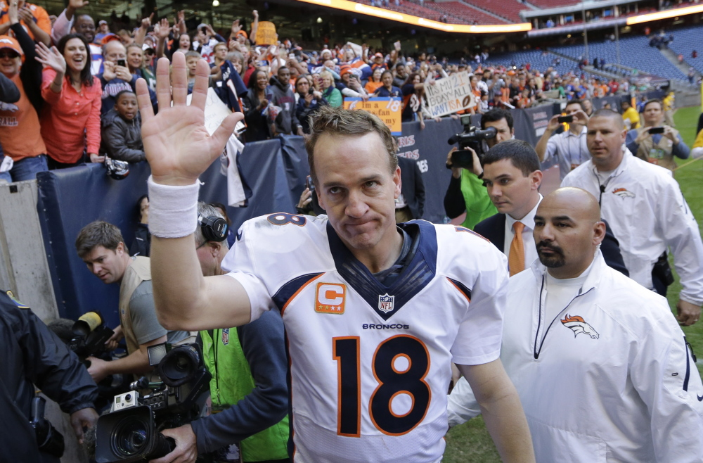 Denver Broncos' Peyton Manning waves to fans following a Dec. 22, 2013, game against the Houston Texans in Houston. Manning threw his 51st touchdown pass of the season to set a new NFL record.