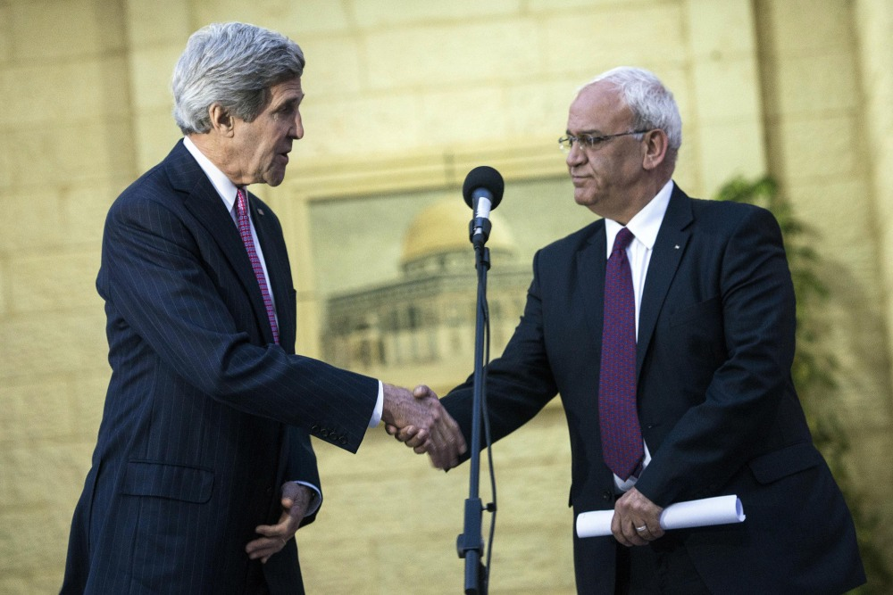 """U.S. Secretary of State John Kerry, left, shakes hands with Palestinian negotiator Saeb Erekat during a press conference after meeting with Palestinian President Mahmoud Abbas at the presidential compound in the West Bank city of Ramallah on Saturday. Kerry said Israelis and Palestinians are committed to settling their differences and are working with """"great intensity and serious purpose"""" to achieve that long-sought goal."""