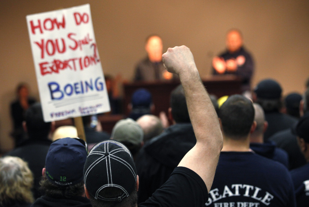 Machinists union members and supporters cheer at a rally asking members to vote against a proposed contract.