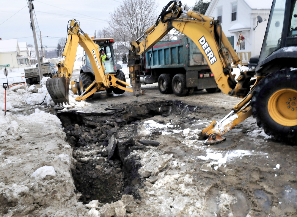 BURST: Workers dig up a portion of Oak Street in Waterville that was closed most of Sunday after a water main break sent water flooding on to Oak Street and Drummond Avenue. Bob Durand of Kennebec Water District said the reason for the flooding or the exact location of the break had not been determined by late afternoon.