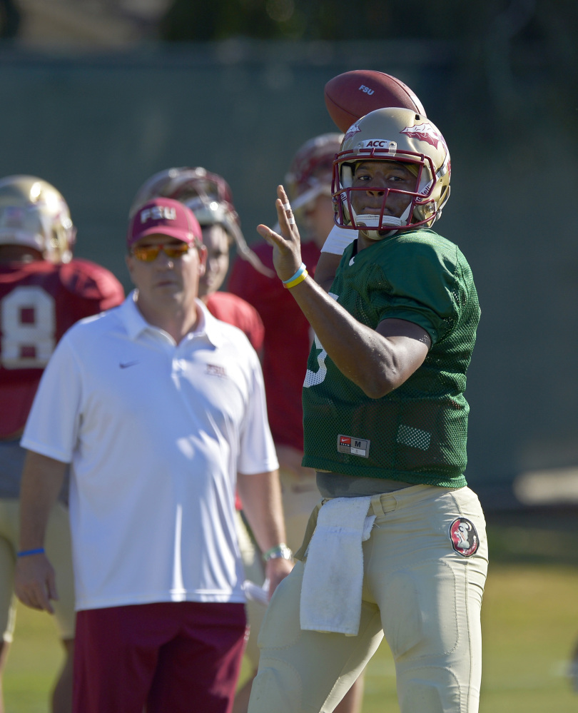 Florida State quarterback Jameis Winston, right, passes as head coach Jimbo Fisher looks on during practice for their BCS Championship game against Auburn, Thursday, Jan. 2, 2014, in Costa Mesa, Calif. (AP Photo/Mark J. Terrill)