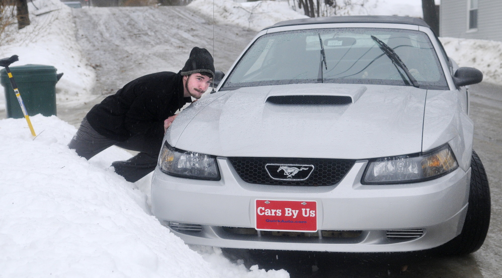 ELEMENTS: Michael Johnston attempts to push John Thiele's car out of a snow bank Monday in Hallowell. Drivers encountered hazardous conditions across Maine while heavy rain fell on already slick roads.