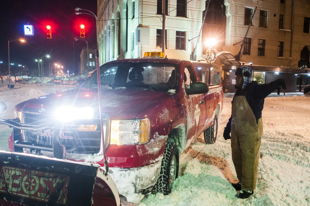 Leroy Griffis, a maintenance supervisor for the Flint Downtown Development Authority directs a snowplow to an assignment where he will clear streets early Monday in downtown Flint, Mich., where a recorded 16.2 inches of snow fell.