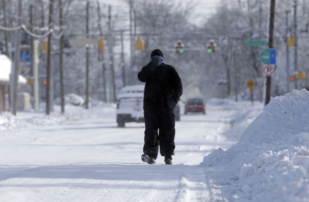 A pedestrian makes his way along a snow packed street in Indianapolis Monday as temperatures hovered around 10 below zero. More than 12 inches of snow fell on Sunday.