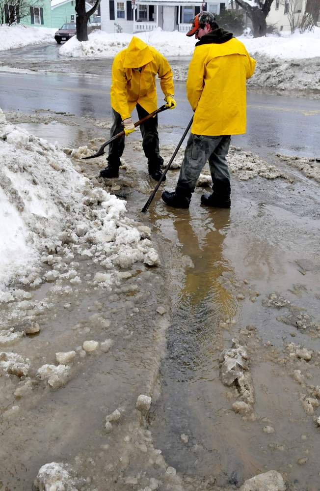 UNPLUGGED: Waterville Parks and Recreation Department employees Steve Buzzell, left, and Sam Green were reassigned Monday to help the city Public Works Department clear storm drains in Waterville.