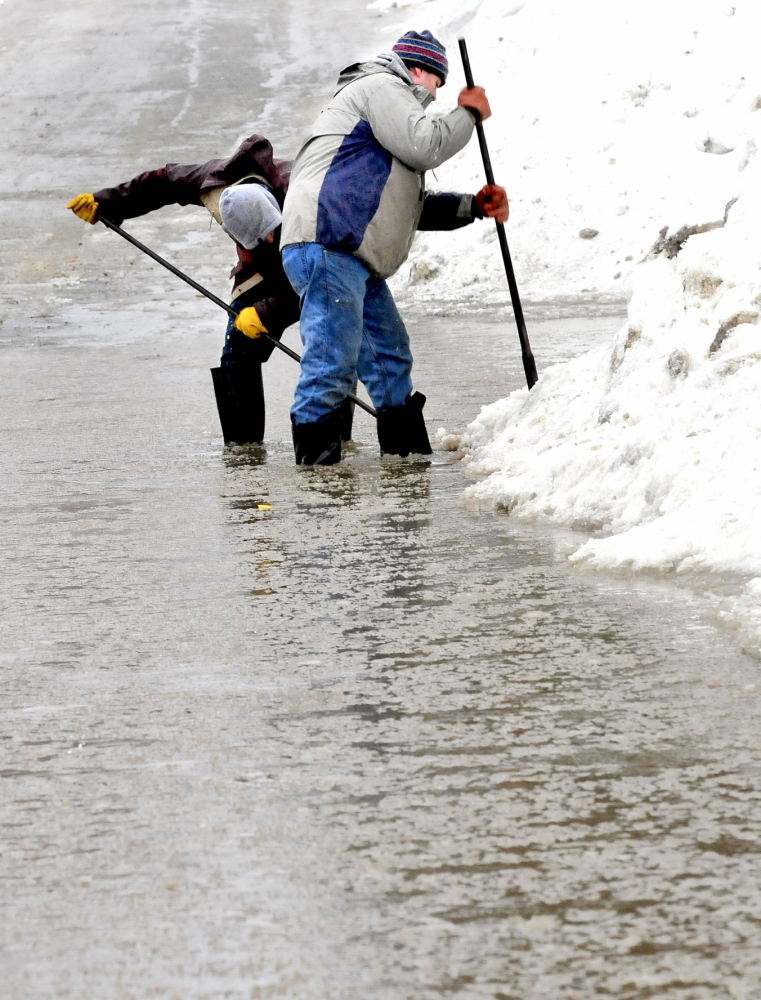 """OVERWHELMED: Maxim Turmelle, left, and his uncle Arthur Turmelle search for a plugged storm drain in Waterville on Monday. """"We called the city but they were overwhelmed with flooding calls so we did it,"""" Arthur Turmelle said."""