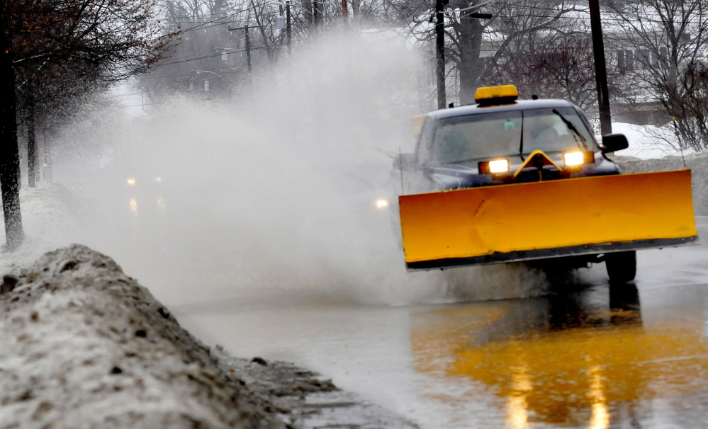 BLAST OFF: A plow truck drives through a flooded street in Waterville sending a rooster tail of spray in its wake on Monday.