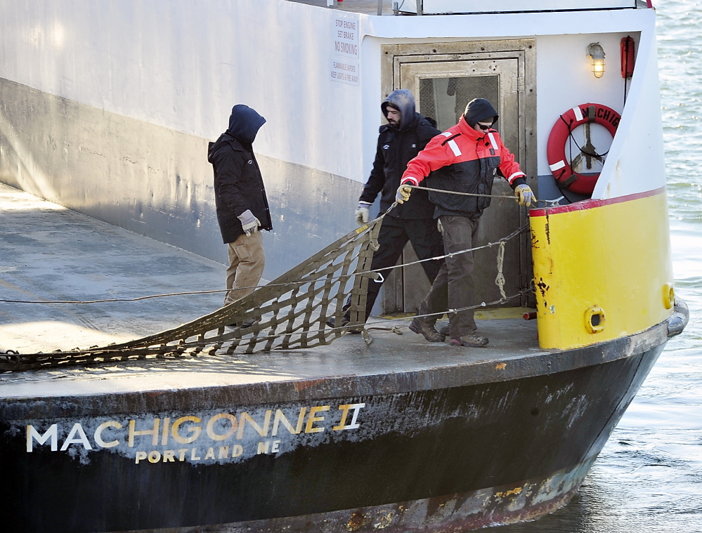 Crew members of the Machigonne II put up a safety barrier in the cold weather as the ferry leaves from the Casco Bay Lines terminal for the islands on Tuesday.