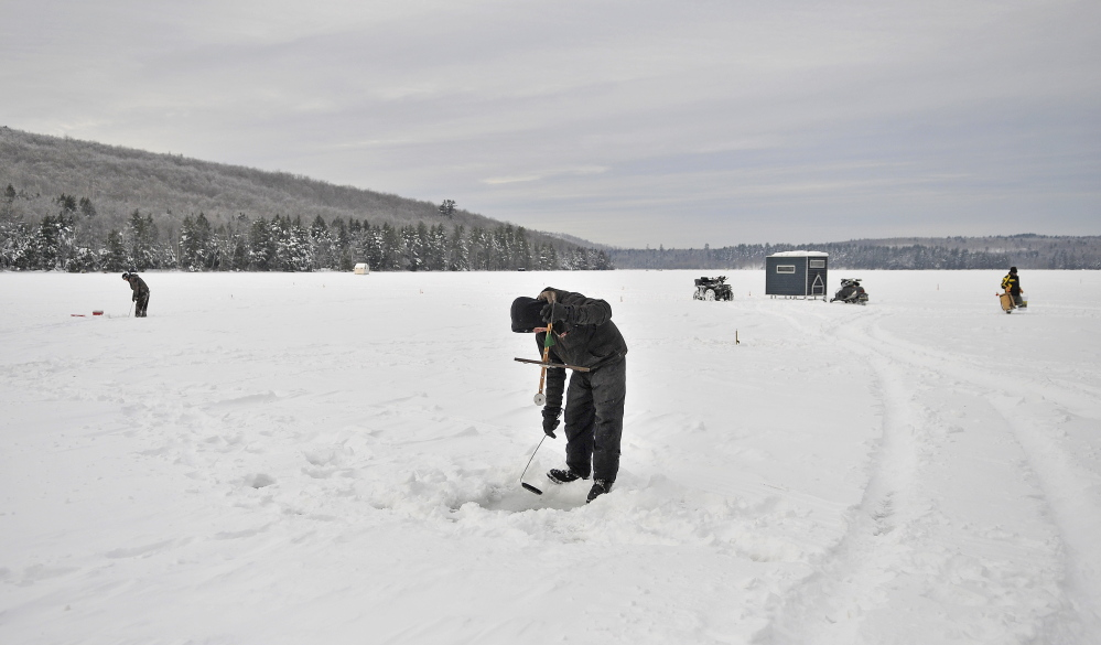 """Staff photo by Michael G. Seamans COLD TRAP: Jeremny Bessey, 19, of Canaan, clears his fishing hole of ice while ice fishing at Lake George Regional Park on the Canaan and Skowhegan town line on Saturday. Bessey arrived at 5am to fish with no bites as of noon. """"It was 20 below zero when I got here. So at least it has warmed up to 1 degrees."""" Said Bessey."""