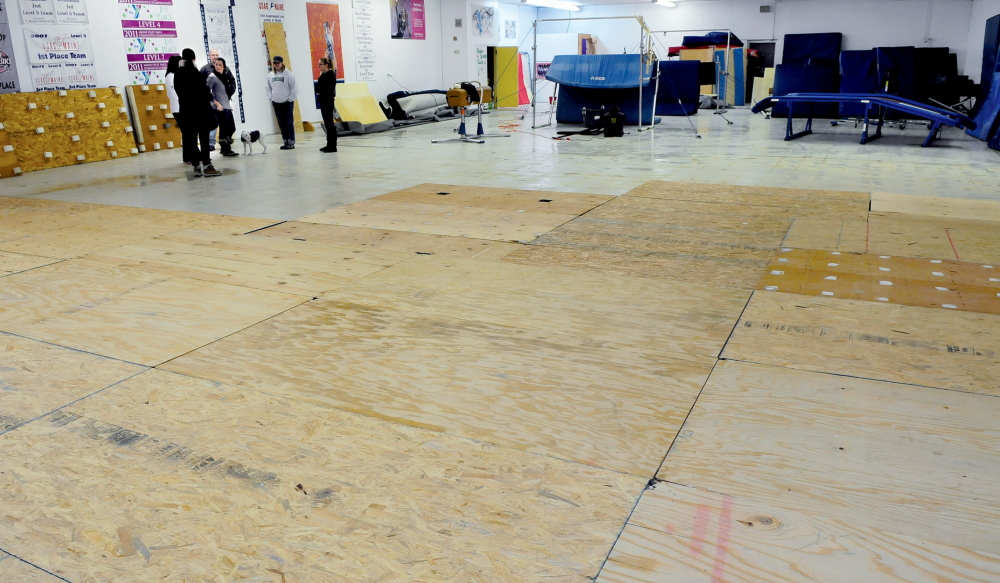 Staff photo by David Leaming SPRING HAS SPRUNG: Owners and employees of Decal Gymnastics talk about the damage caused after water from the roof of the Farmington business poured over the spring flooring, foreground, mats, carpets and equipment Monday evening.