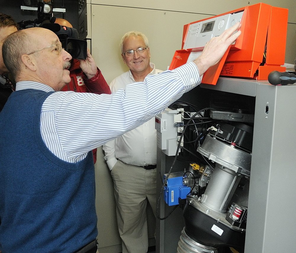 NATURAL GAS: City Manager William Bridgeo, left, flips the switch on the new natural gas fired boiler on Tuesday at the boiler room in the basement of Augusta's City Center. Jim Bolduc, a sales manager at Viessman, the company that made the boiler, center, watches the ceremonial switch flipping.