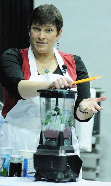 AG SHOW: Cynthia Finnemore Simonds, of Mindful Mouthful, talks about making smoothies featuring kale and blueberries during a cooking demonstration at the Maine Agricultural Trades Show on Wednesday at the Augusta Civic Center.