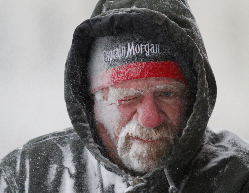 Allan Umscheid, owner of Yards By Al, feels the bitter wind and catches drifting snow on his face as he runs a snowblower in Lawrence, Kan., on Sunday.