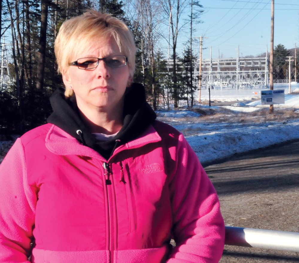 QUIET PLEASE: Benton resident Sue Blaisdell stands at the gate to the CMP substation near her home off the Albion Road on Thursday. Blaisdell and other neighbors have complained about noise levels coming from the substation.