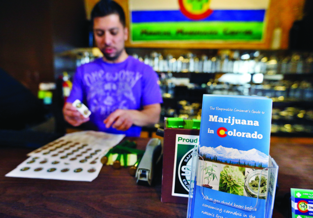 General manager David Martinez labels containers of retail marijuana, behind a sales bar fitted with a brochure available to customers, at 3D Cannabis Center in Denver, Tuesday Dec. 31, 2013. Colorado is making final preparations for marijuana sales to begin Jan. 1, a day some are calling