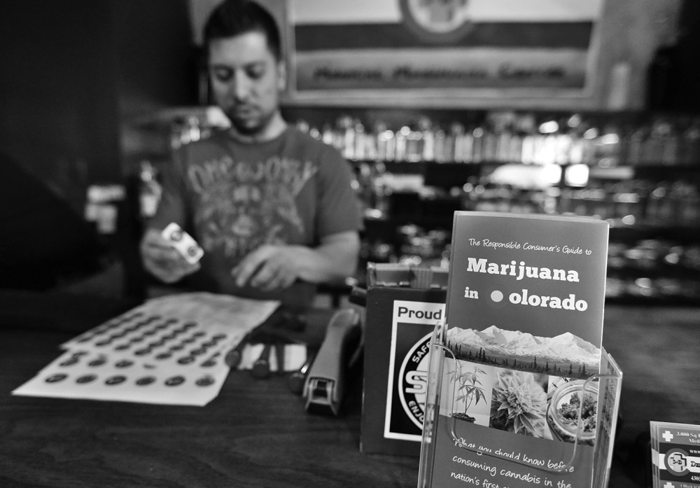 "General manager David Martinez labels containers of retail marijuana, behind a sales bar fitted with a brochure available to customers, at 3D Cannabis Center in Denver, Tuesday Dec. 31, 2013. Colorado is making final preparations for marijuana sales to begin Jan. 1, a day some are calling ""Green Wednesday."" The 3D Cannabis Center will be open as a recreational retail outlet on New Year's Day. (AP Photo/Brennan Linsley)"