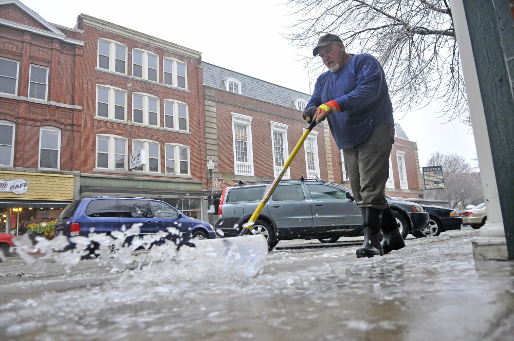 ICE WORK: Bruce Heath, with KB Property Care, clears the sidewalks Saturday on Main Street in Waterville. More ice has covered central Maine, making travel a dangerous adventure.