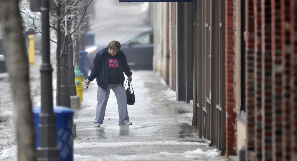 keeping balance: A woman tries negotiate the ice-covered sidewalk on Main Street in downtown Waterville on Saturday.