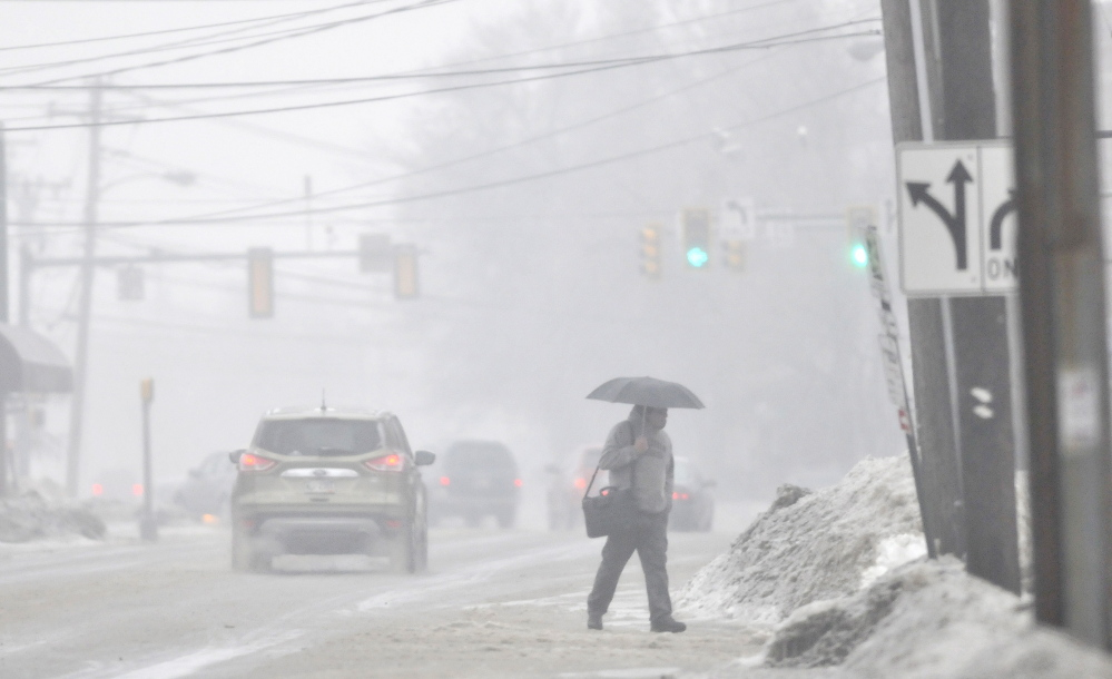 ICE walk: A pedestrian crosses Elm Street in Waterville on Saturday.