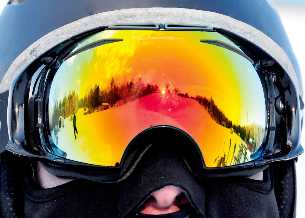 """GOOD VIEW: One of the slopes at Titcomb Mountain Ski Area is reflected in the goggles of snowboarder Pete Roberts at the Farmington facility. Roberts has patronized Titcomb since the early '90s and continues with his daughters. """"This is a great local area resource that can't be beat,"""" Roberts said."""