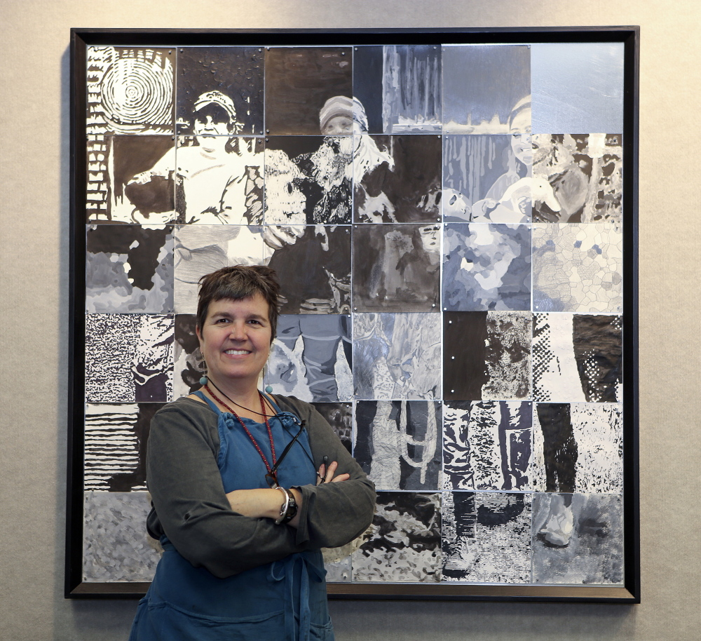 Growers in a grid: University of Maine at Augusta art instructor Susan Bickford poses in front of a portrait of the Perry family from Winterberry Farm in Belgrade. It's one of 10 portraits of local organic farmers assembled from squares completed by students at 10 central Maine schools. Bickford organized the project, which culminates in an exhibit opening Thursday at UMA's Danforth Gallery.