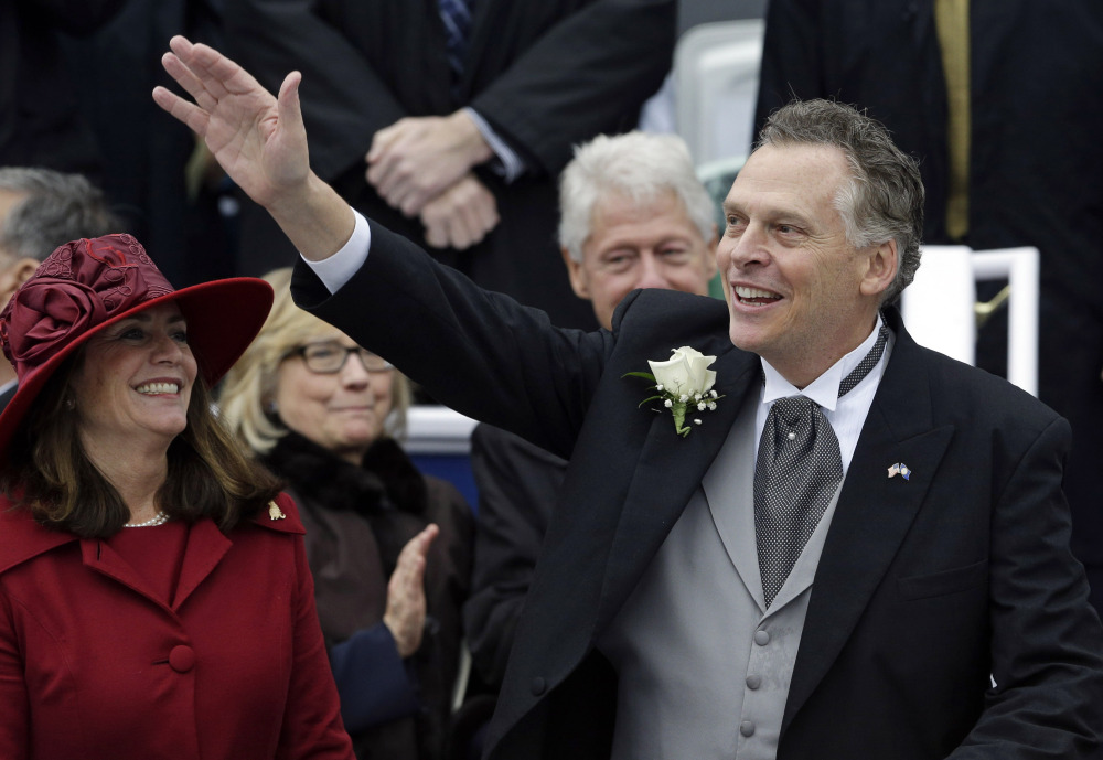 Virginia Gov. Terry McAuliffe, right, waves to supporters alongside his wife Dorothy during inaugural ceremonies at the Capitol in Richmond, Va. on Saturday. Former U.S. Secretary of State Hillary Rodham Clinton, left, and former U.S. President Bill Clinton look on in the background. McAuliffe is the 72nd governor of Virginia.