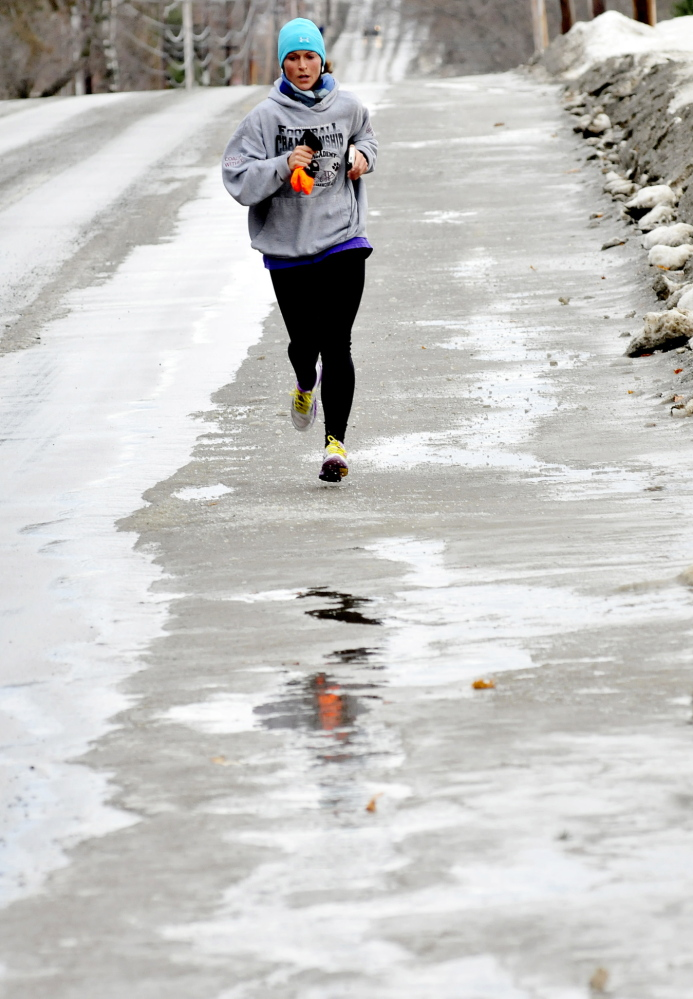 "Staff photo by David Leaming SLOPPY RUN: Lindsey Welch runs through slush, water and ice in Waterville on Sunday, Jan. 12, 2104. ""Today is not as bad as Saturday except for my wet feet,"" Welch said."